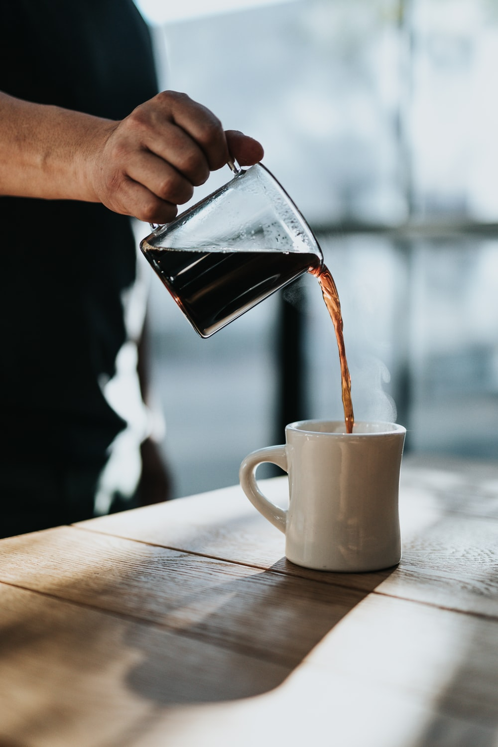 person pouring black coffee in white ceramic mug placed on brown wooden table during daytime