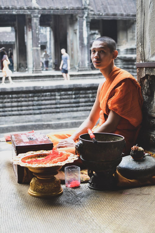 monk sitting near gray pillar