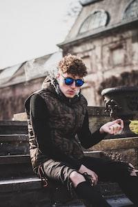 smoking man in black and brown camouflage zip-up vest