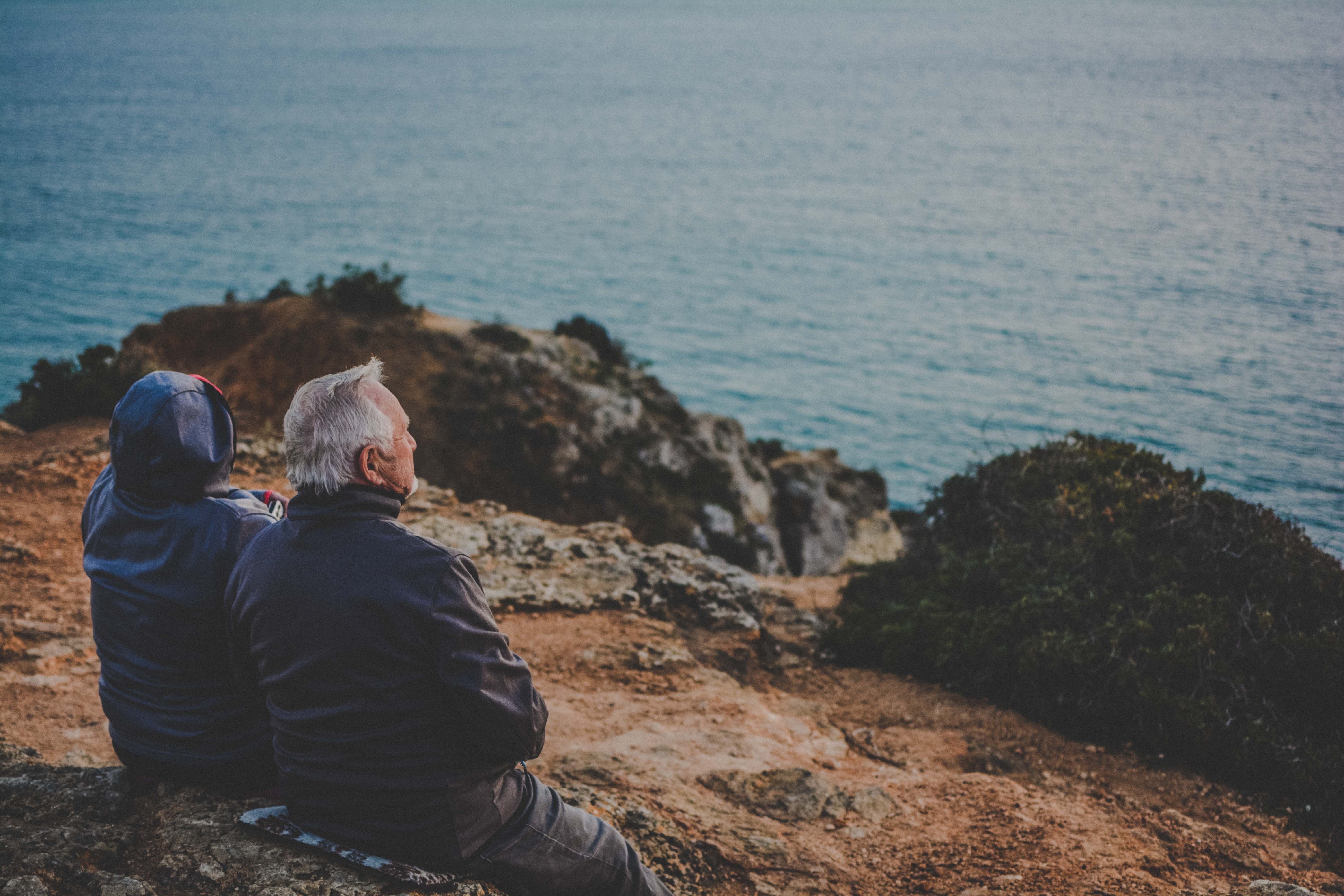 two person sitting on rock staring at body of water during daytime