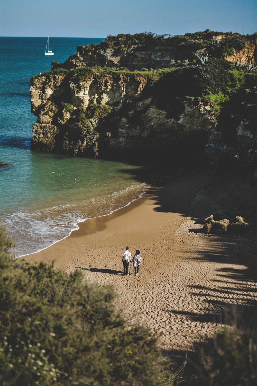 two person standing near seashore