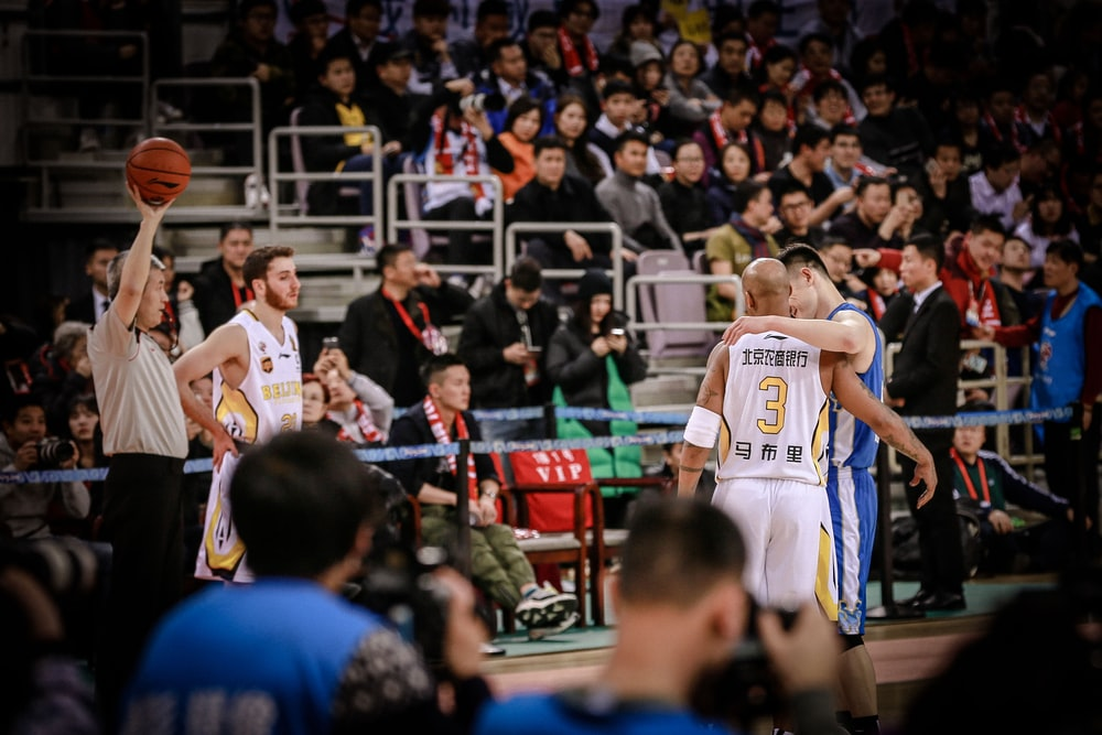 two basketball players about to hug each other at the court
