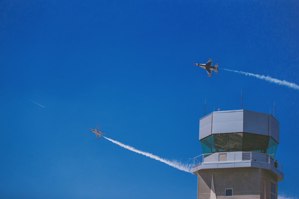 two jet planes flying over gray building during daytime