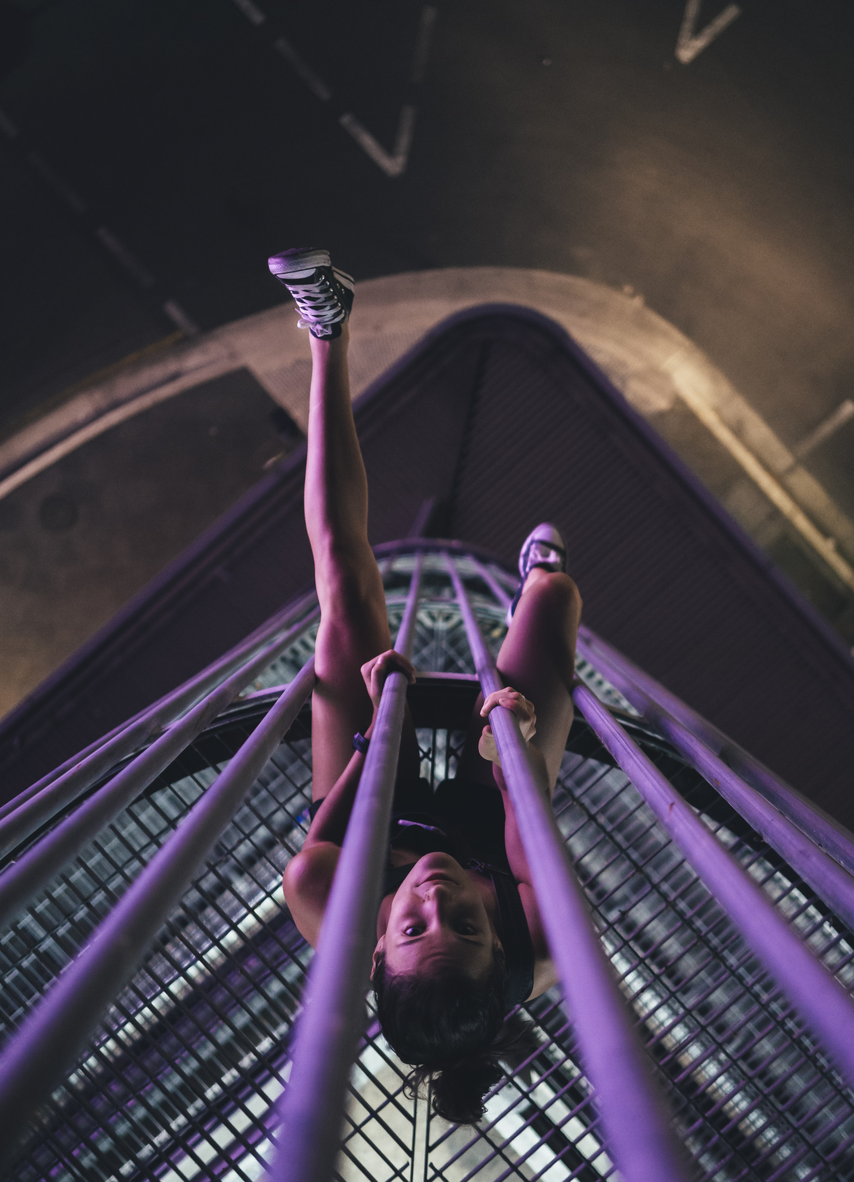 woman on purple metal tower during nighttime
