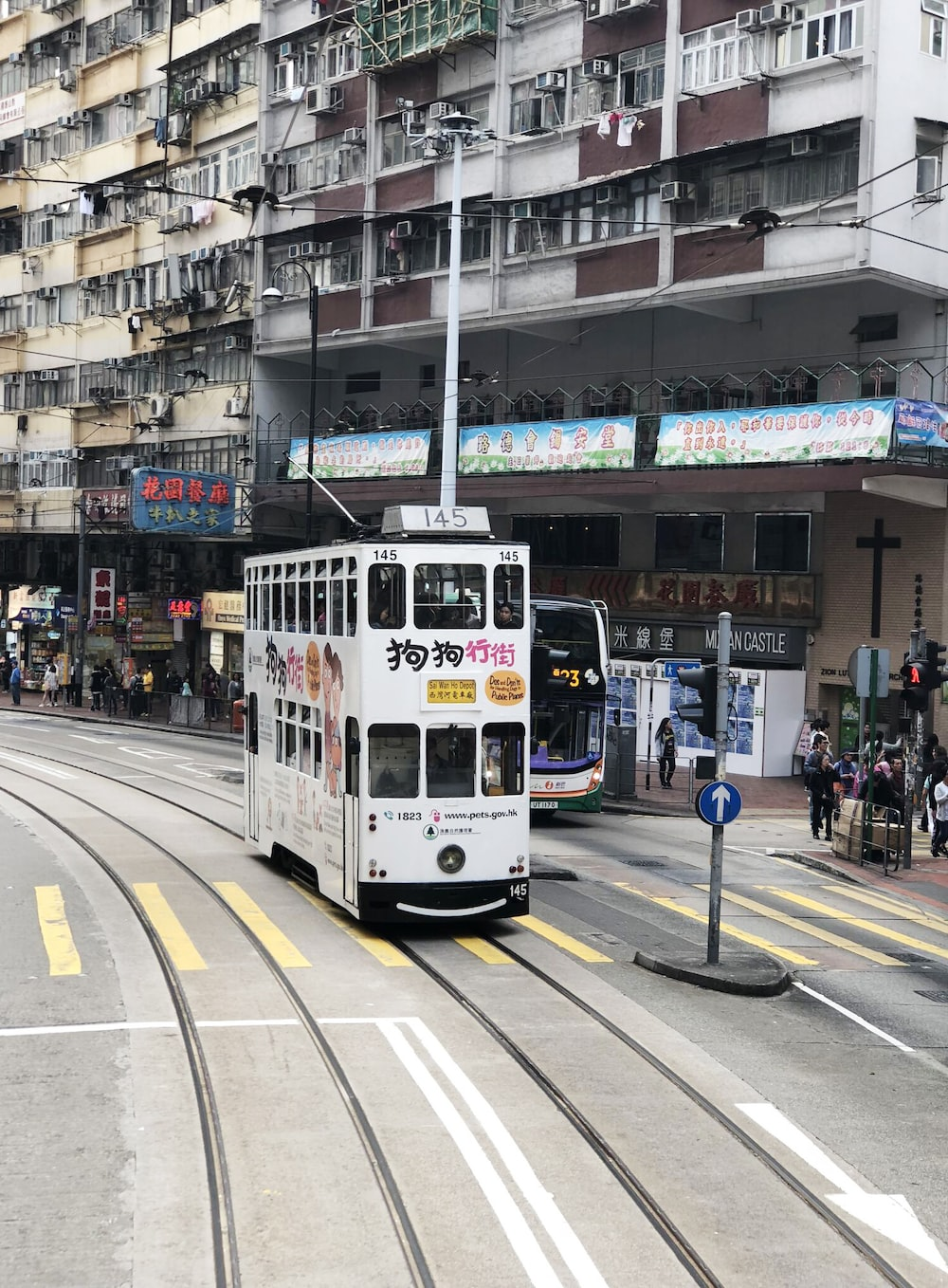 white double-decker bus near white and brown high-rise building at daytime