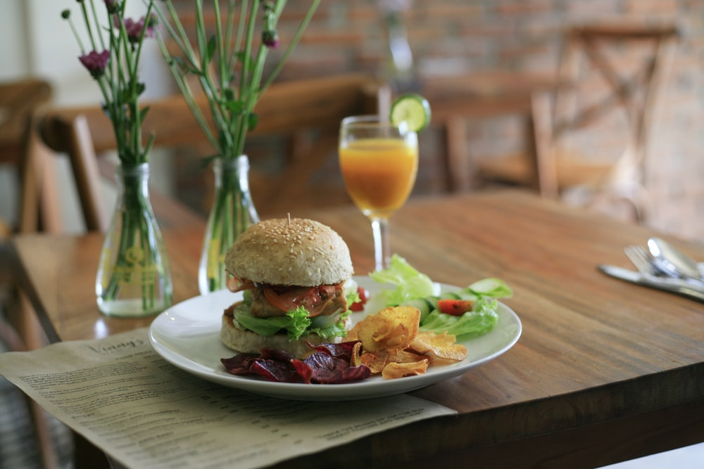 shallow focus photography of hamburger on white ceramic plate
