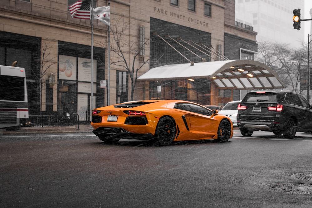 orange coupe on road