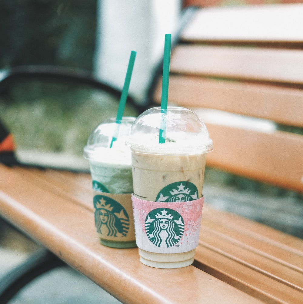 two Starbucks cups on bench