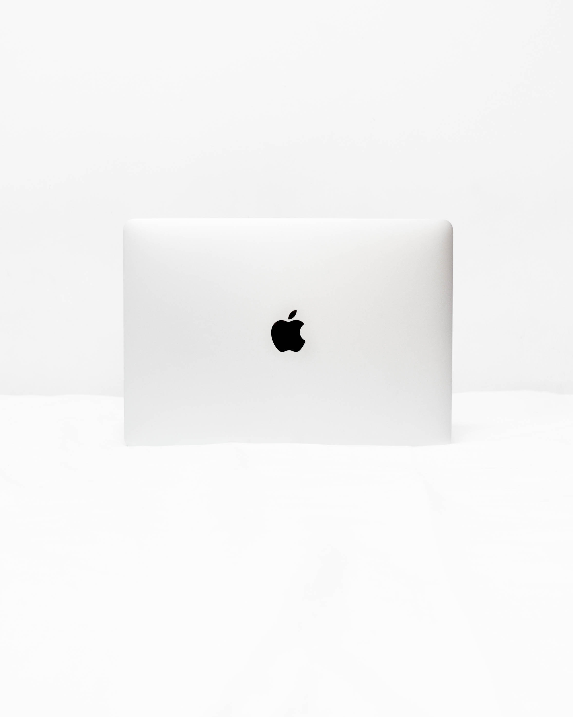 MacBook White open on white surface