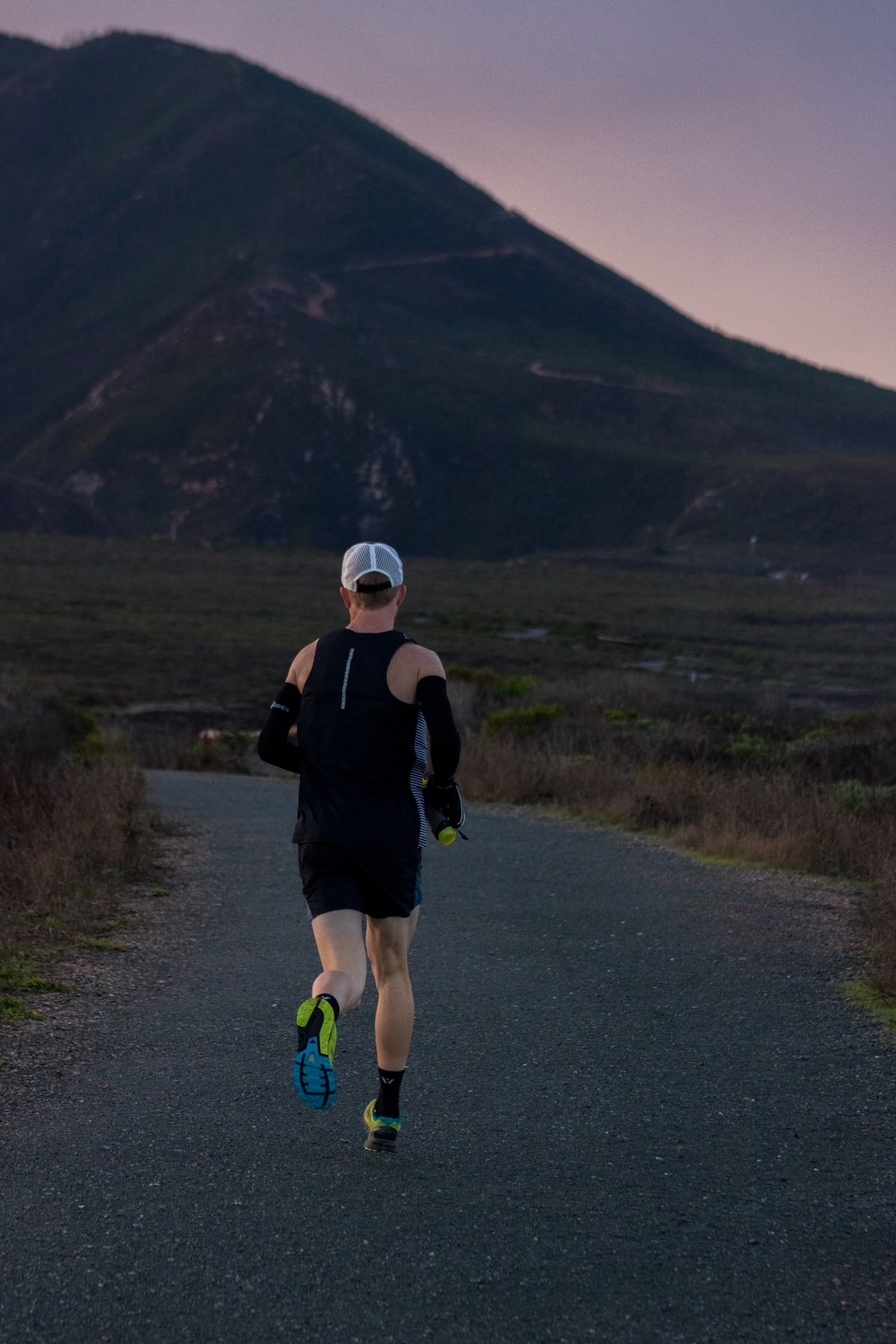 woman jogging on gray road across mountain during daytime