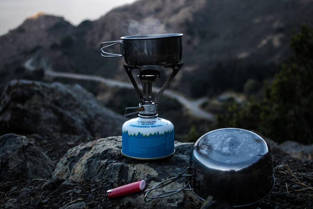 selective focus of blue and gray camping gas burner and cooking pan on cliff