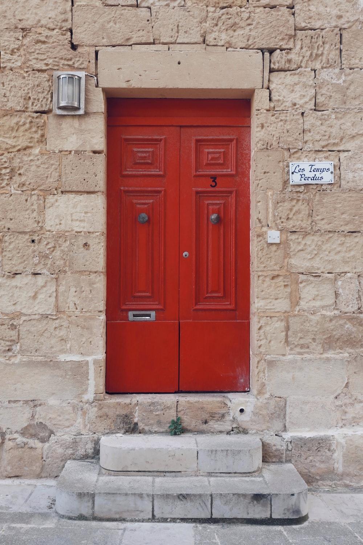 two red doors in beige brick house