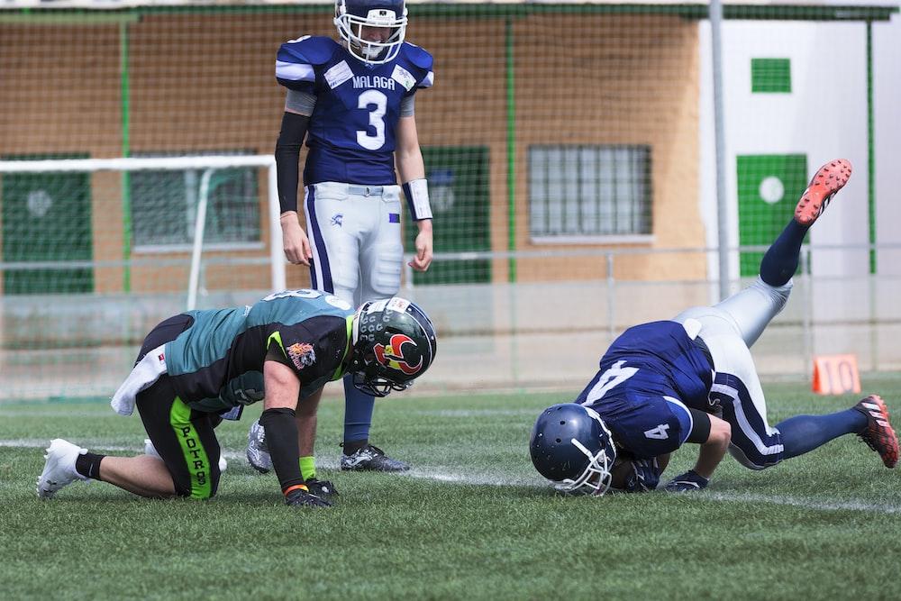 three American football standing on grass field