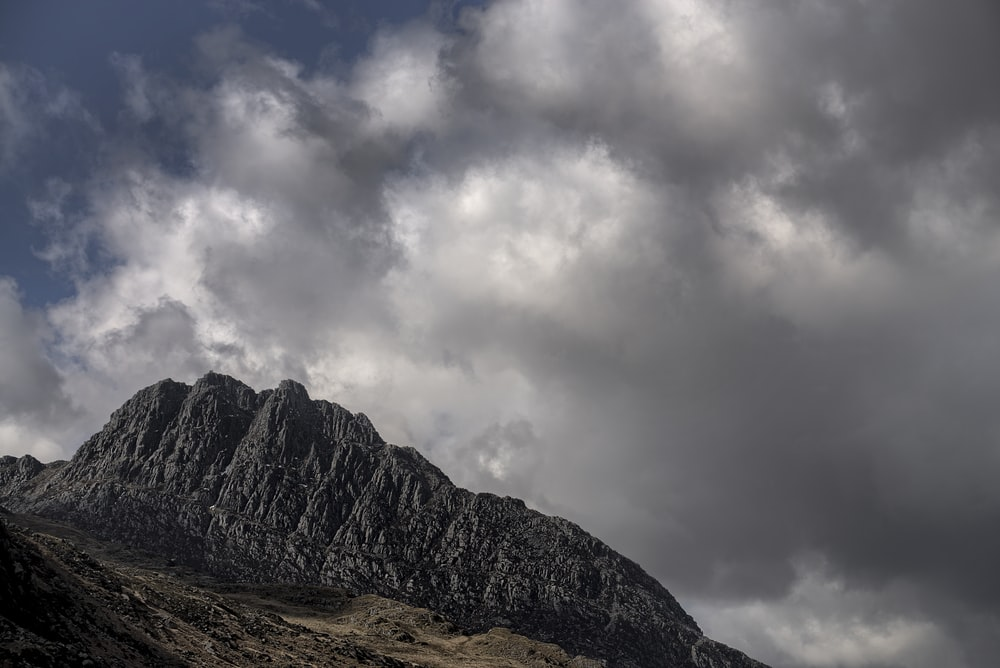 grey mountain under blue and grey cloudy sky