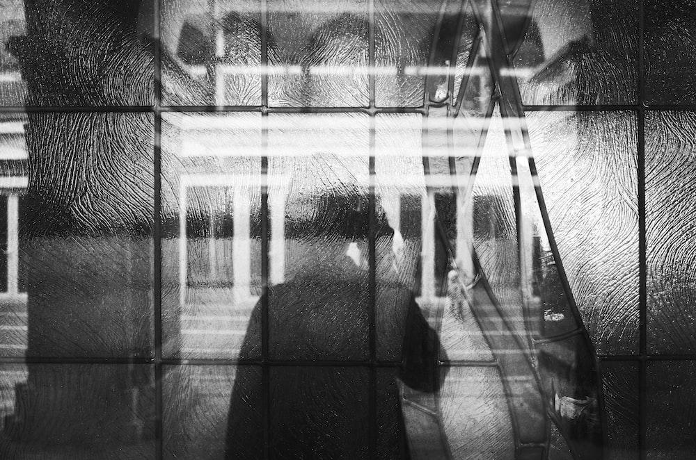 silhoutte of woman on window glass panes