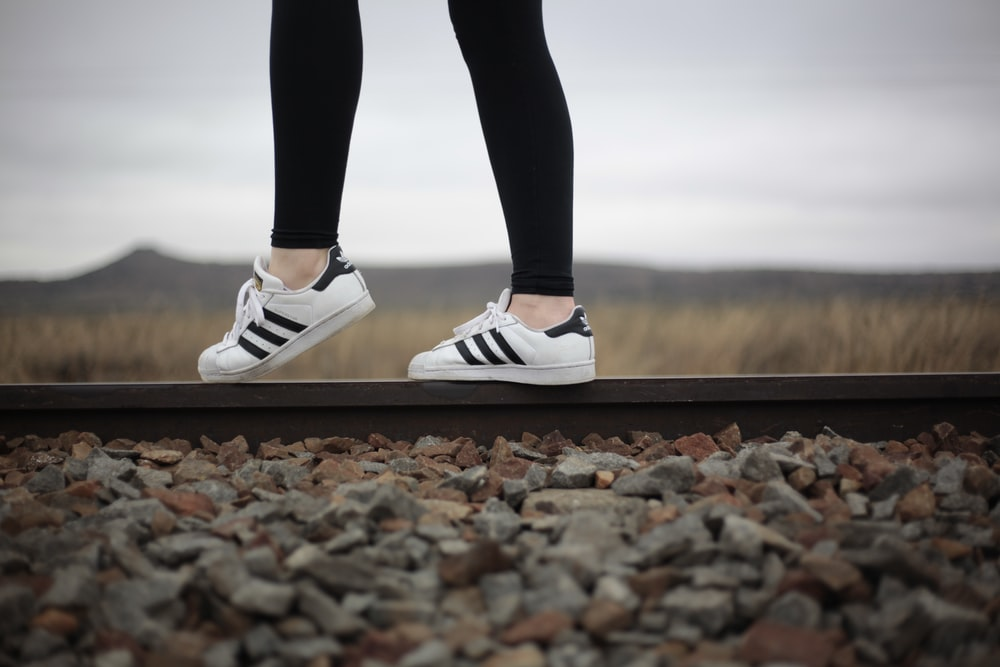 person wearing white-and-black adidas superstar