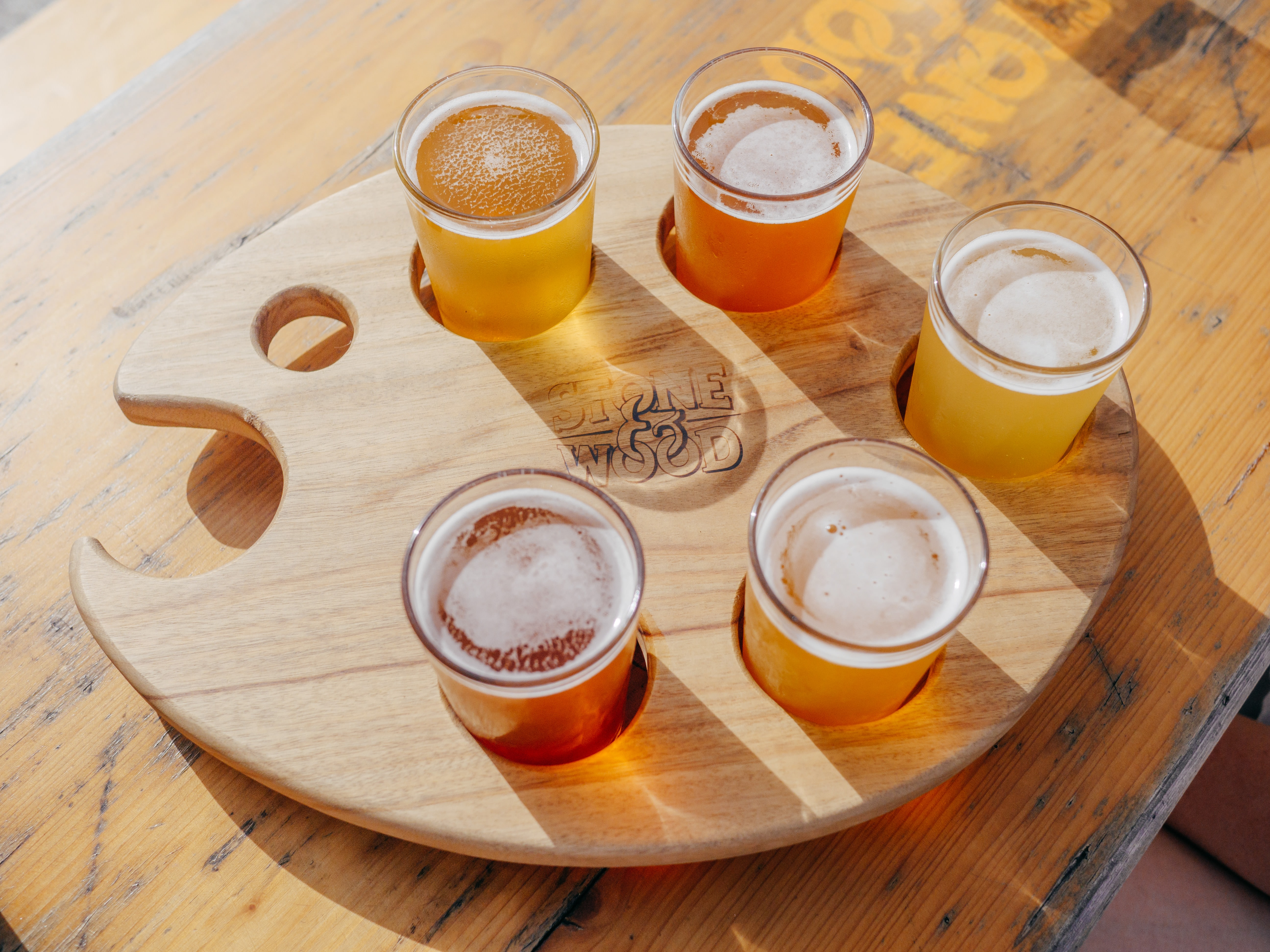 five poured drinking glasses on brown wooden tray
