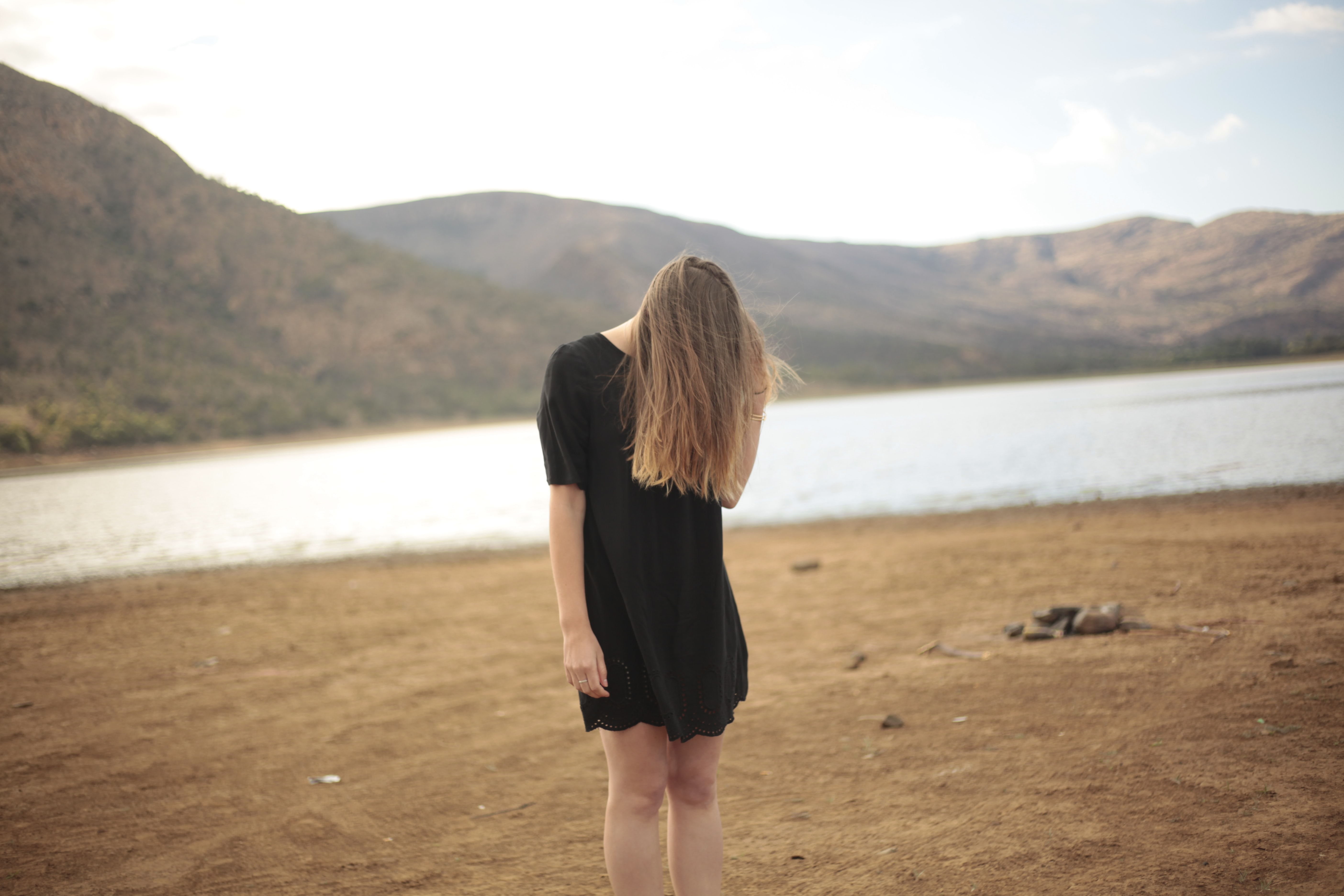 woman in black dress standing in front of lake