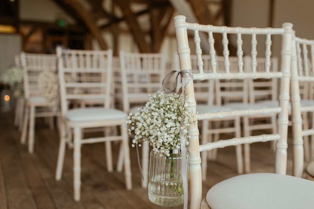 white petaled flowers on jar hang in chair - Sposarsi al tempo del coronavirus