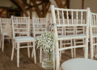 white petaled flowers on jar hang in chair