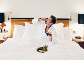 man wearing bathrobe eating on bed