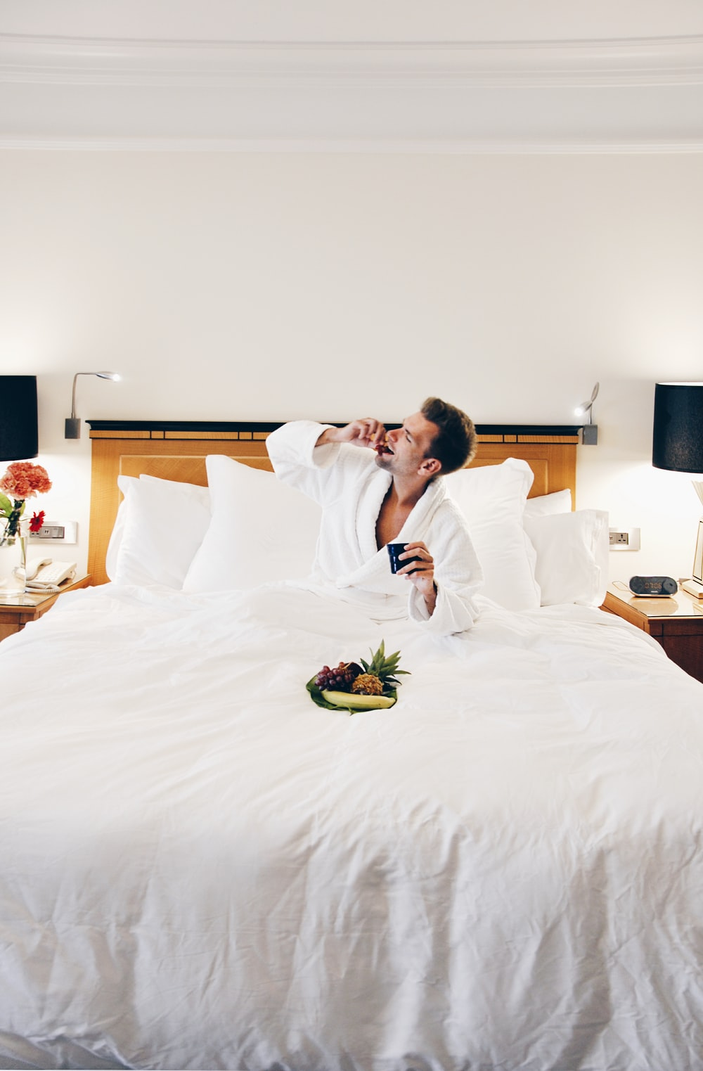 man wearing bathrobe eating on bed