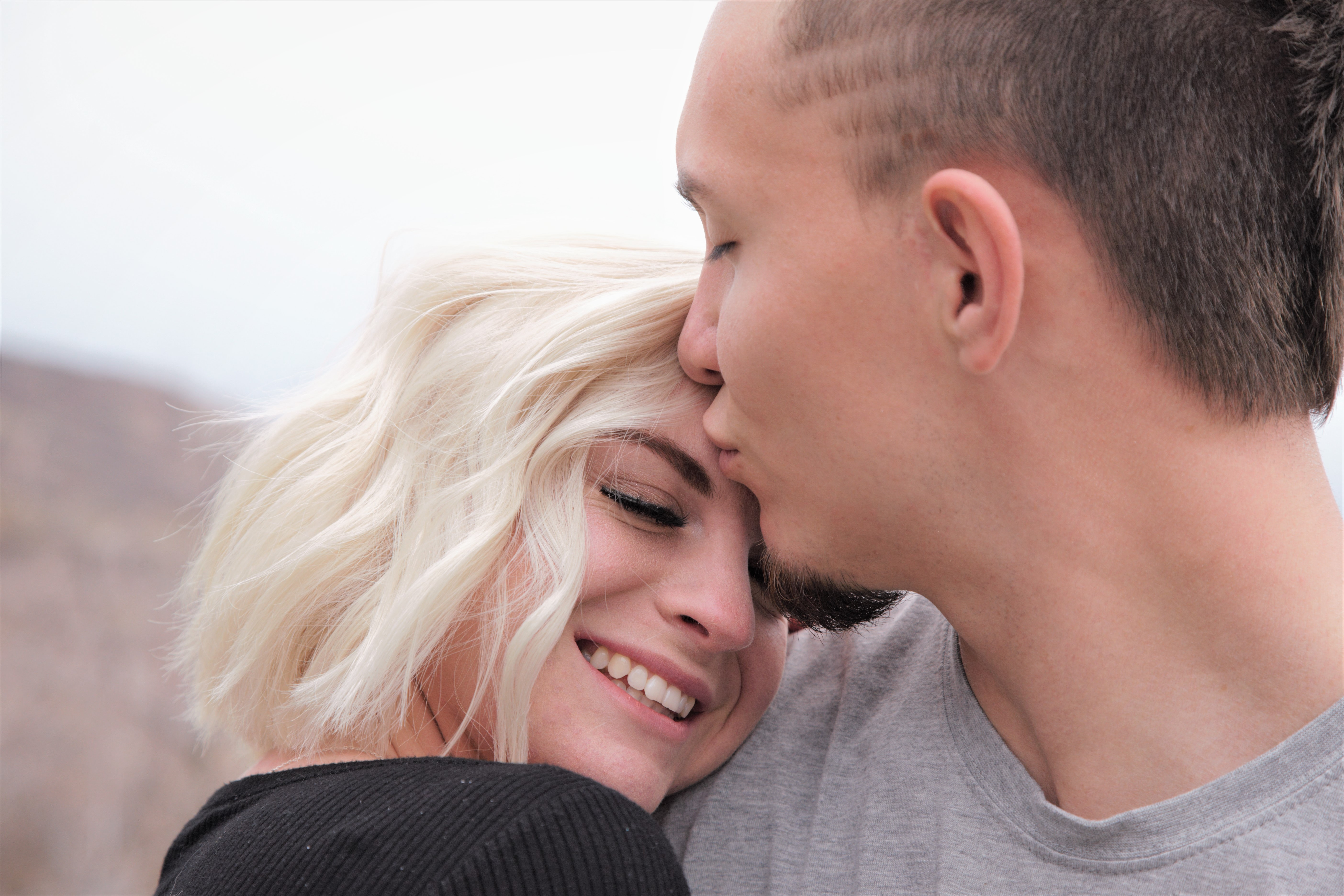 man kissing woman's forehead