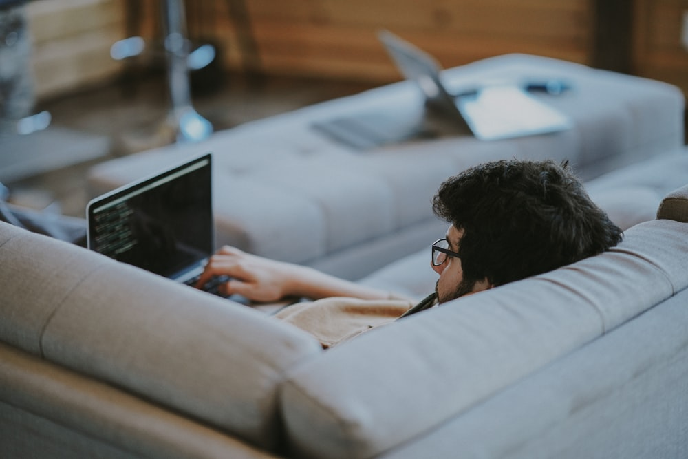 man lying on couch while using laptop computer