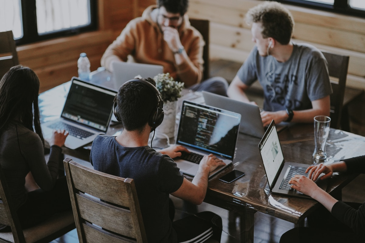 Photograph of 5 startup people sitting around a table with laptops.