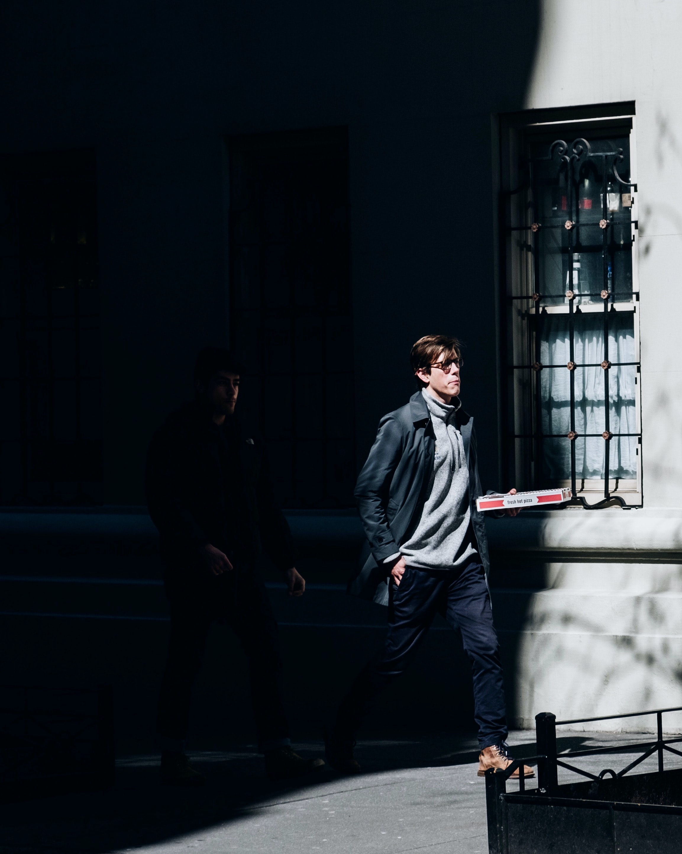 man walking while holding box during daytime