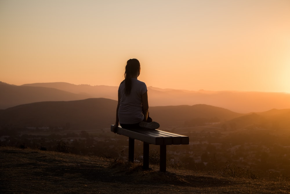 woman sitting on bench over viewing mountain