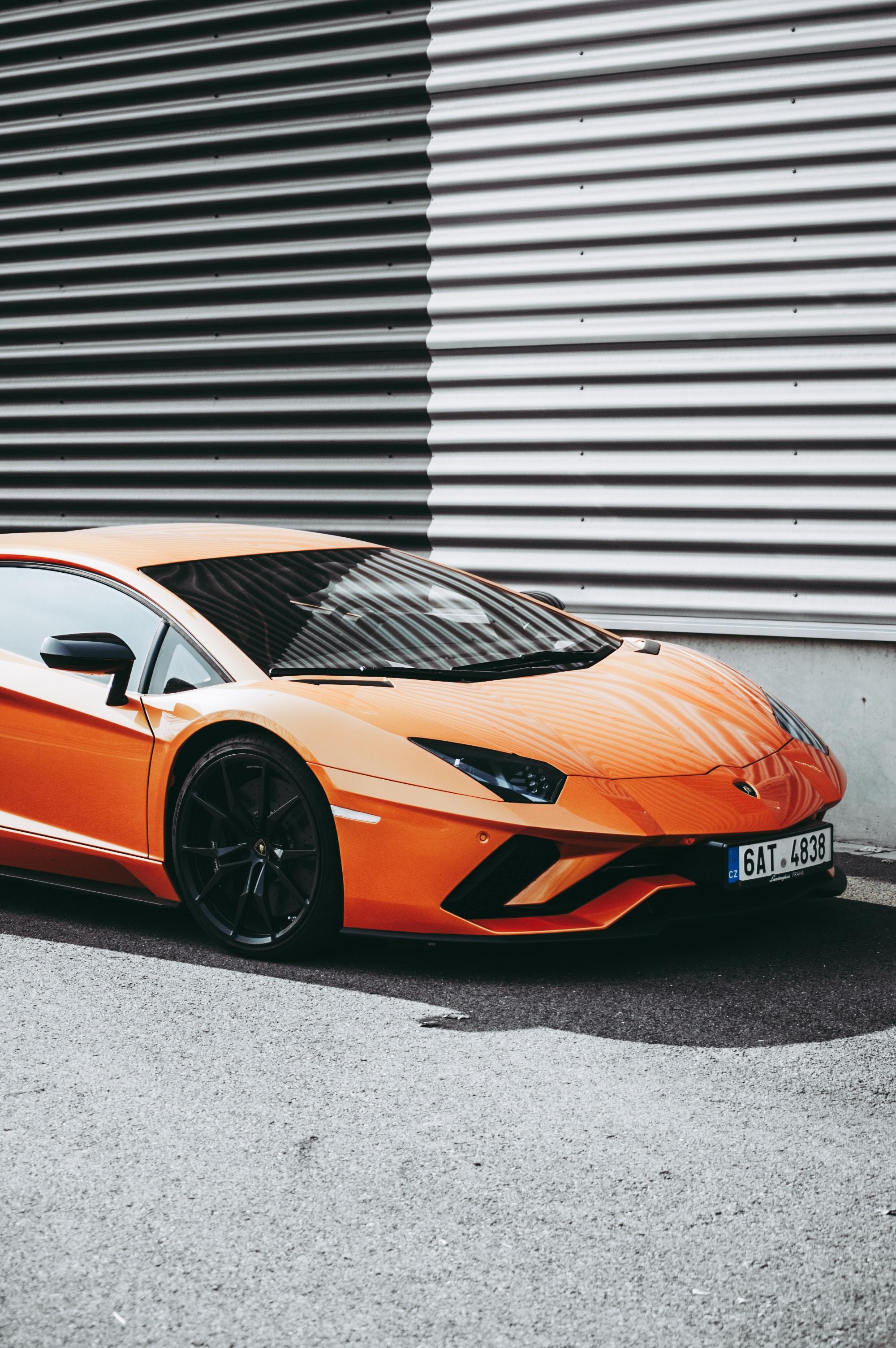 orange Lamborghini sports coupe parked near corrugated wall at daytime