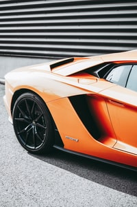 focus photography of parked orange sports car
