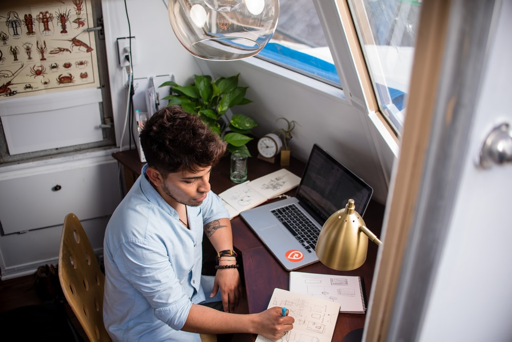 man sits while writing in front of MacBook