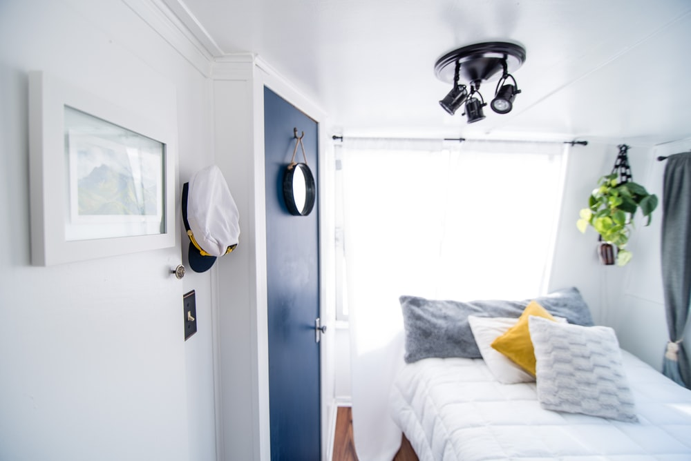 four pillows on quilted white bed near blue door and window with white curtain inside well-lighted room
