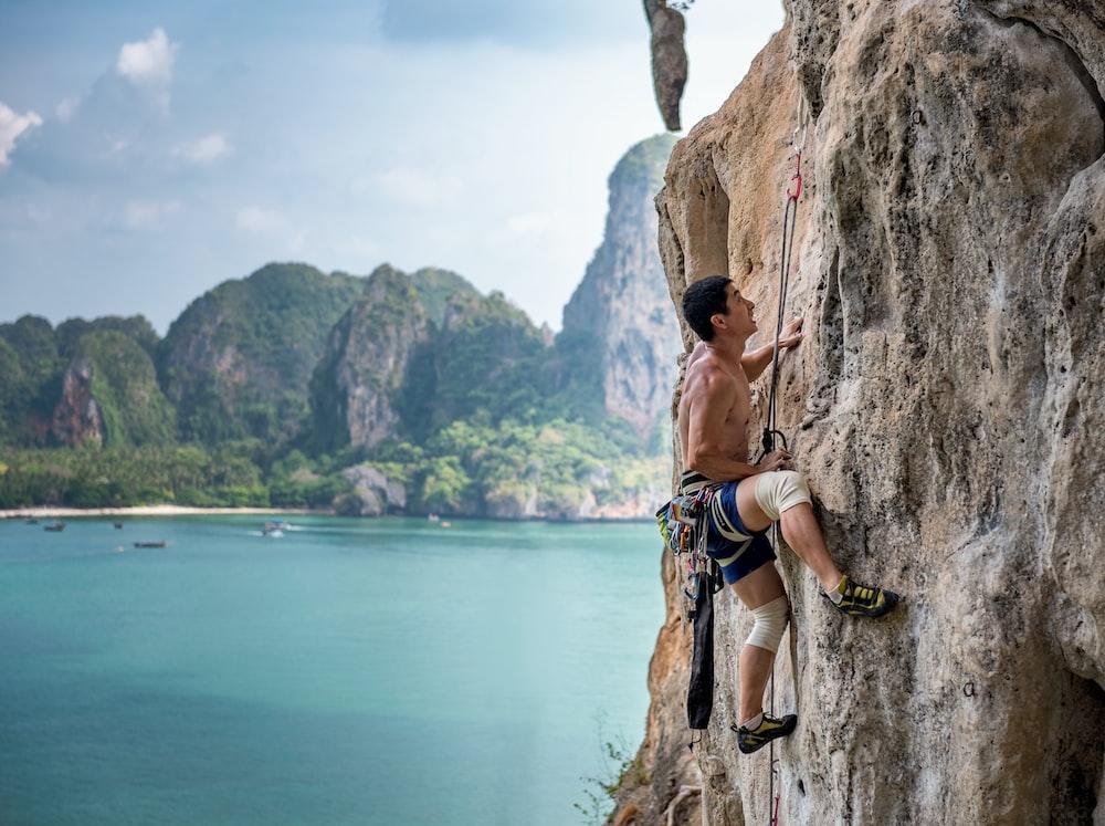 man wearing brown shirt mountain climbing at daytime