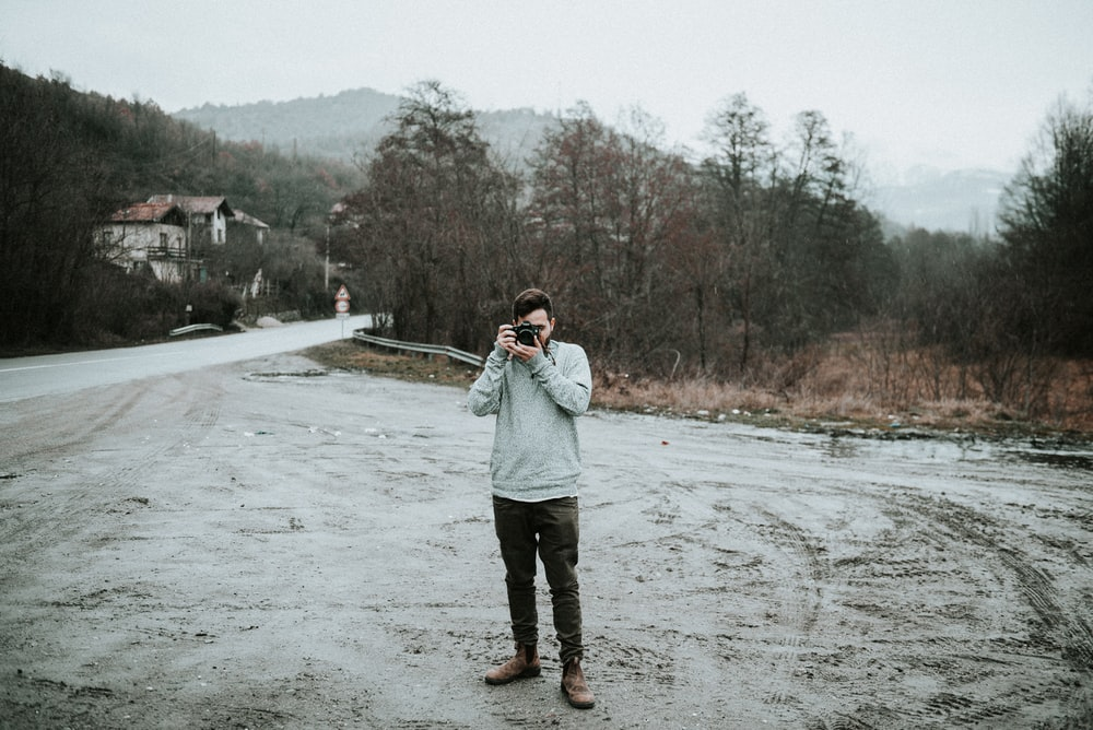 man holding camera in snow-covered road