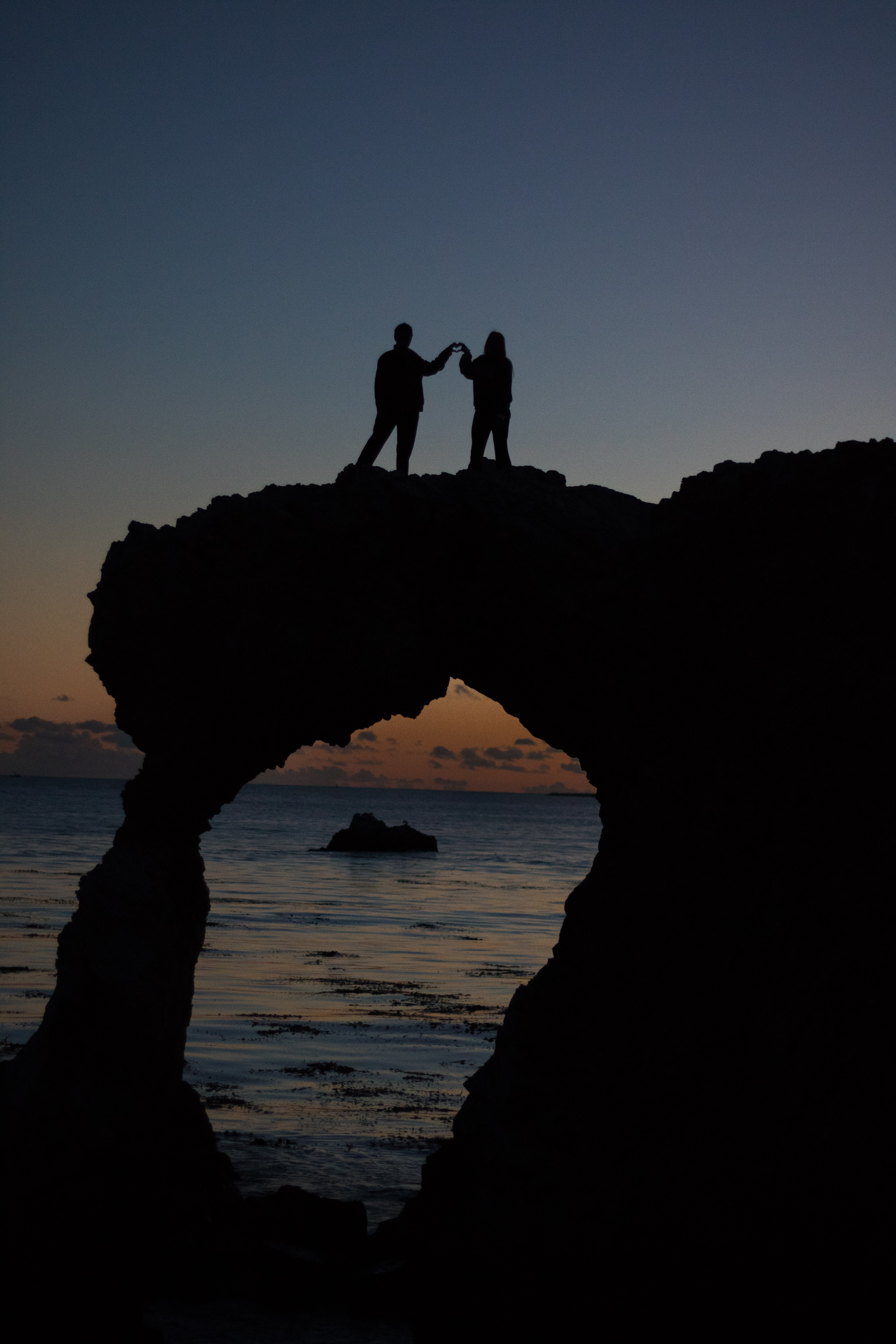 silhouette of two persons atop a rock formation near the ocean