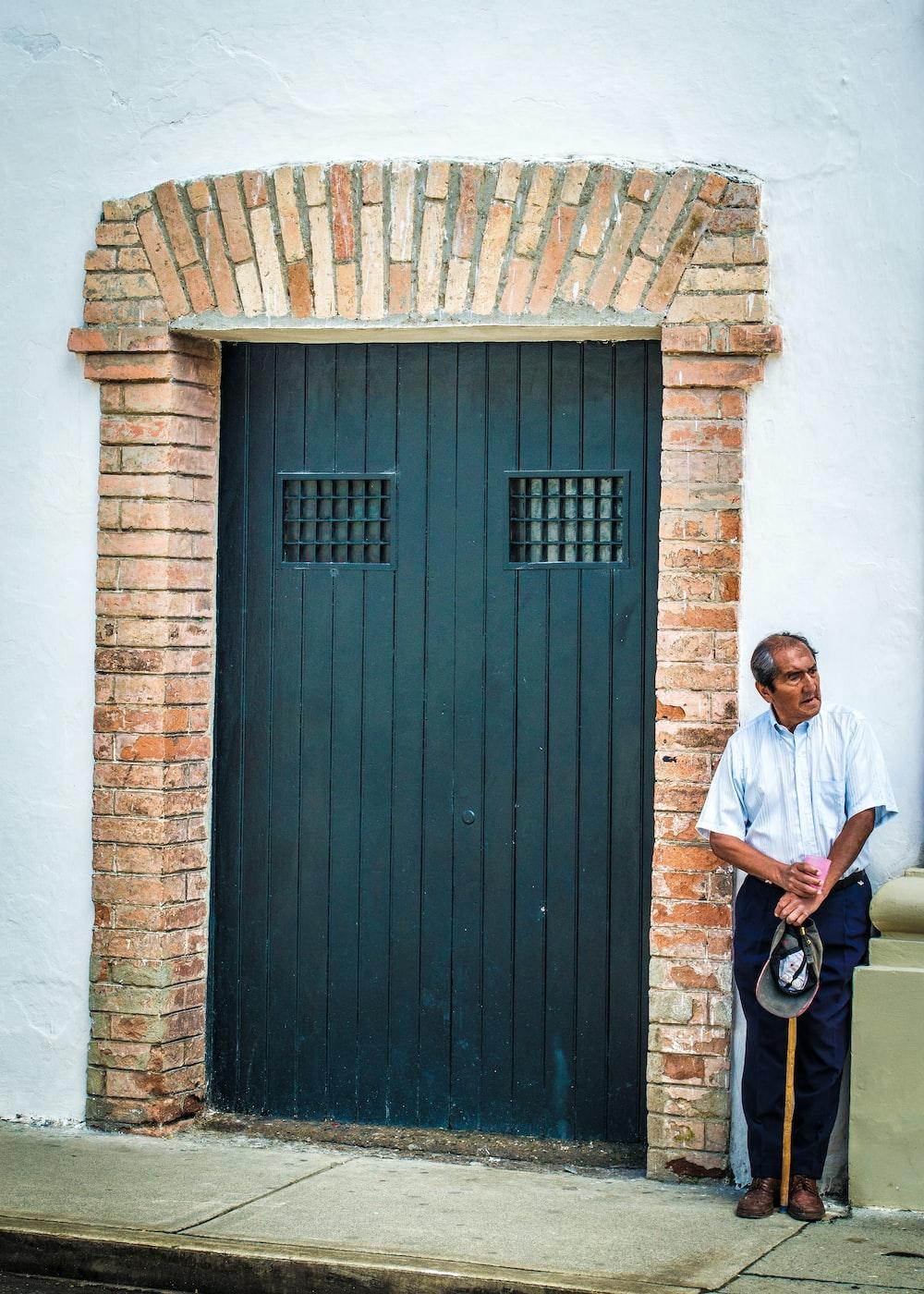 man in white shirt standing next to wooden door