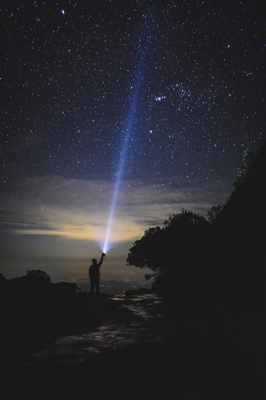 man holding flashlight pointing towards sky