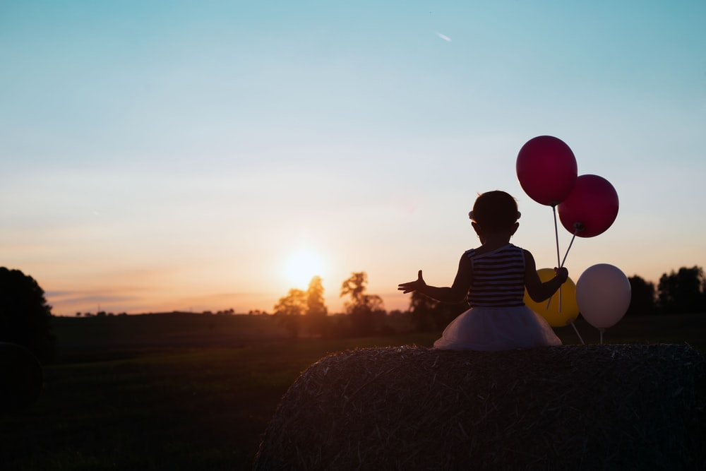 girl holding four assorted-color balloons during sunset