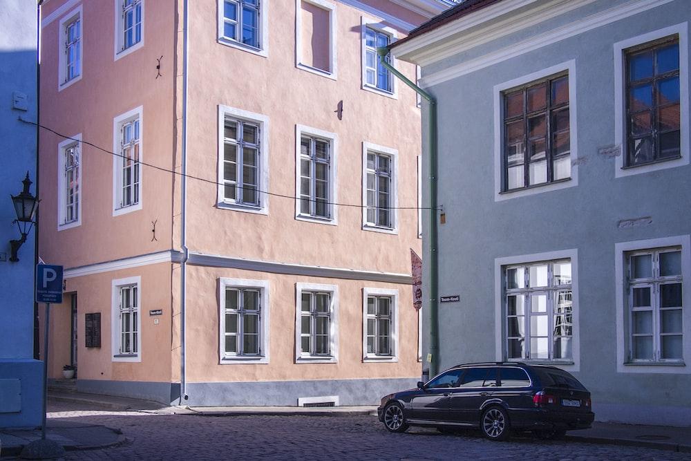 black 5-door hatchback near brown and white concrete building