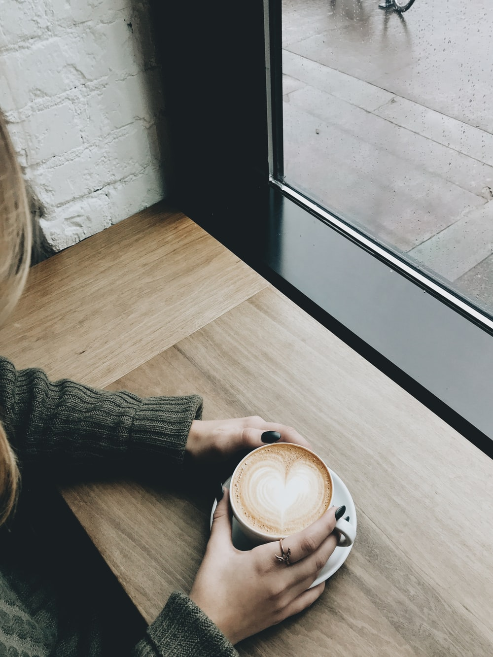person holding cappuccino on brown wooden desk
