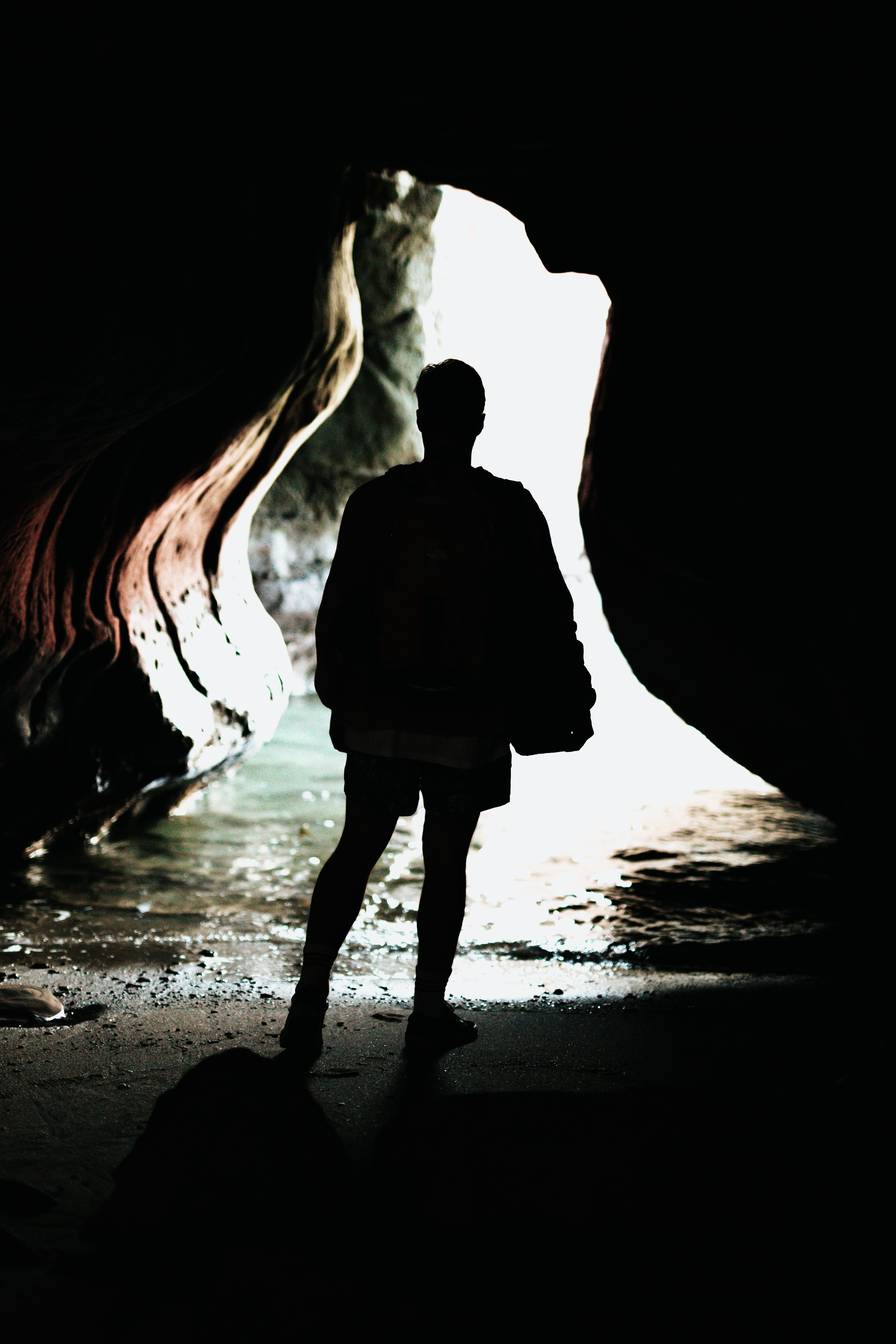 silhouette photo of person standing in front of blue body of water inside cave during daytime