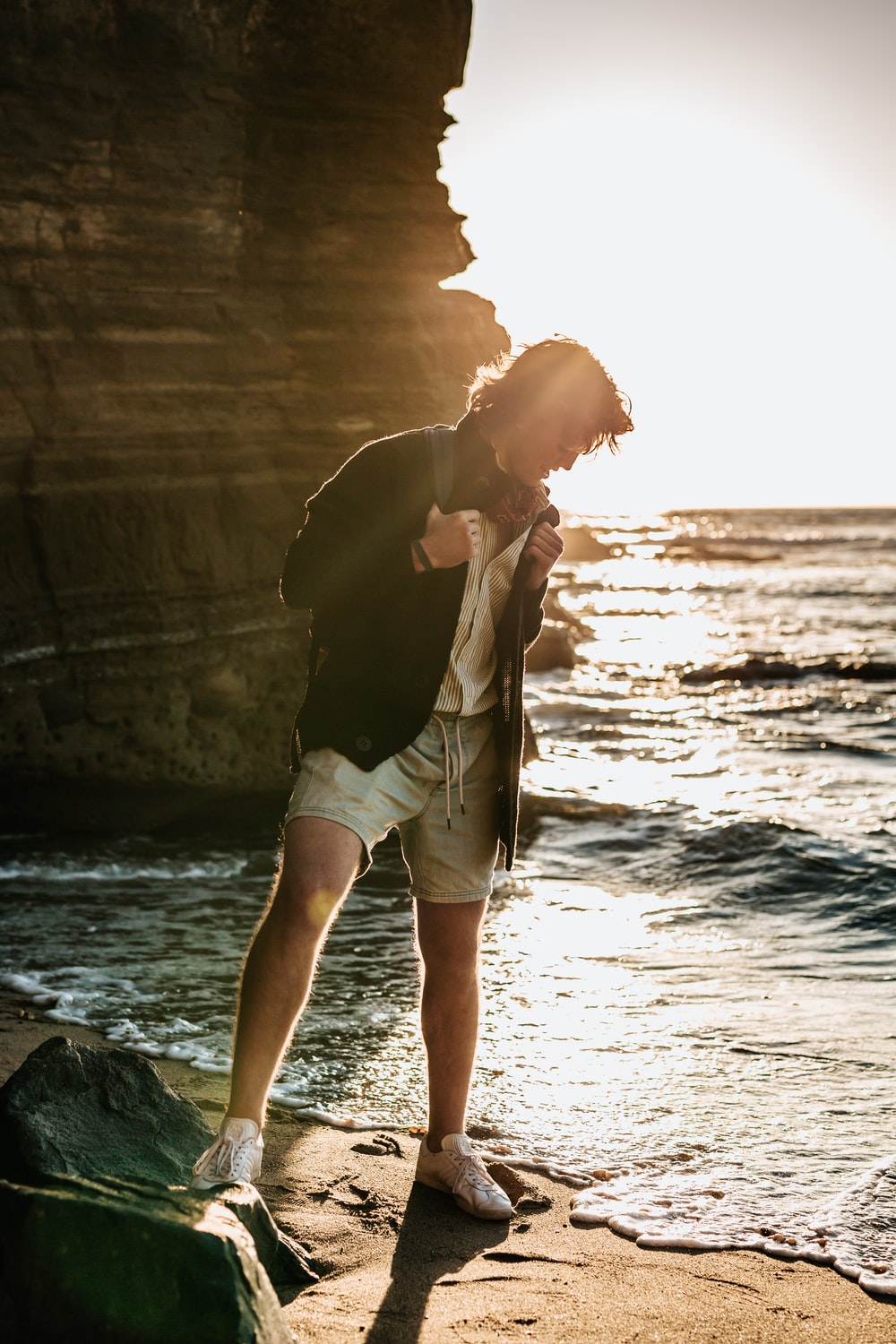 man standing on seashore near rock formation during daytime