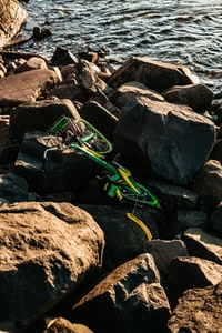 green bicycle surrounded by rocks