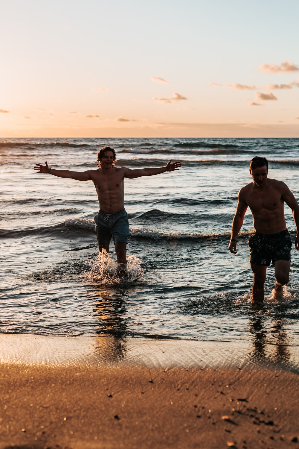 two men standing at shore during golden hour