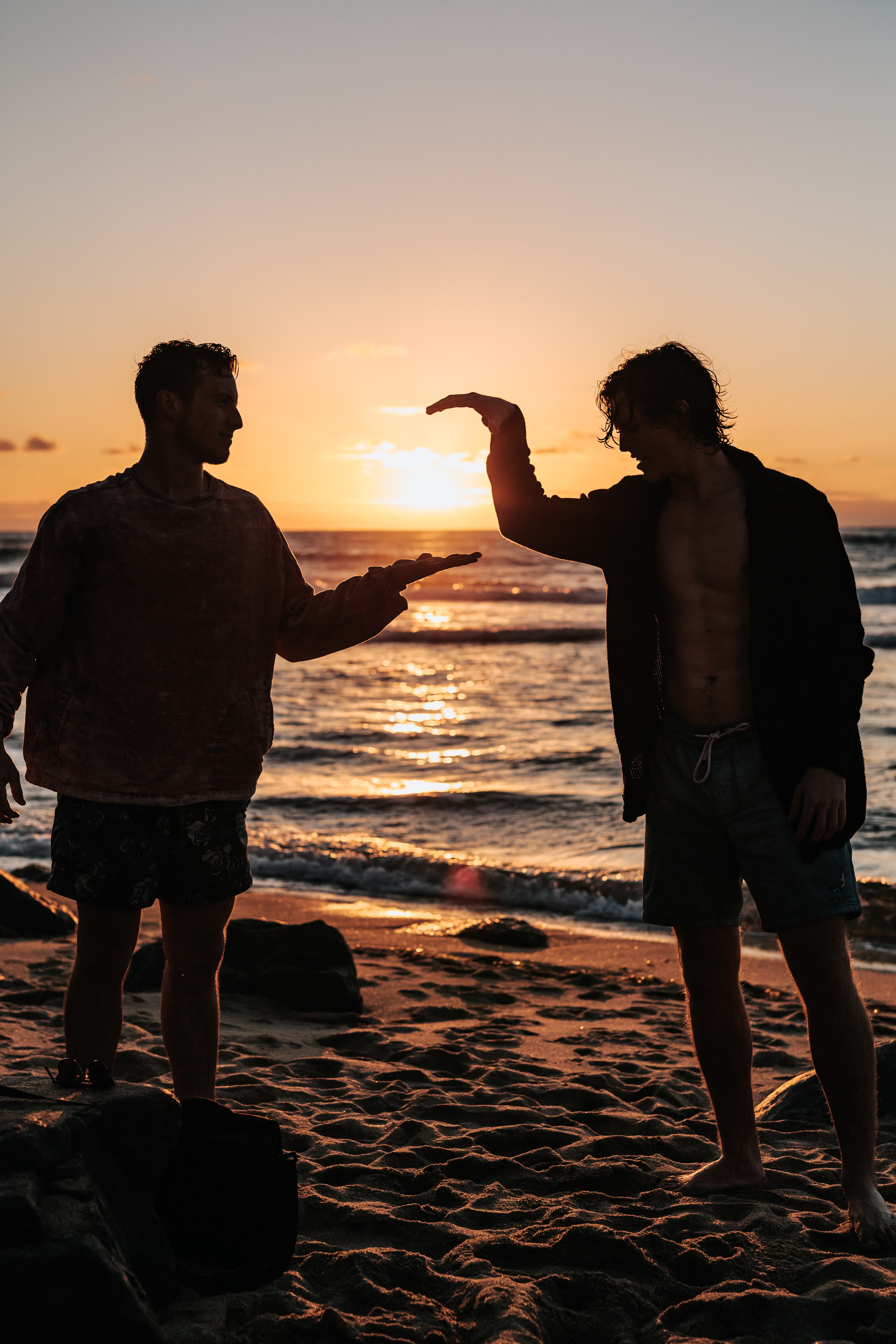 close-up photo of two men shaking hands near beach at sunset