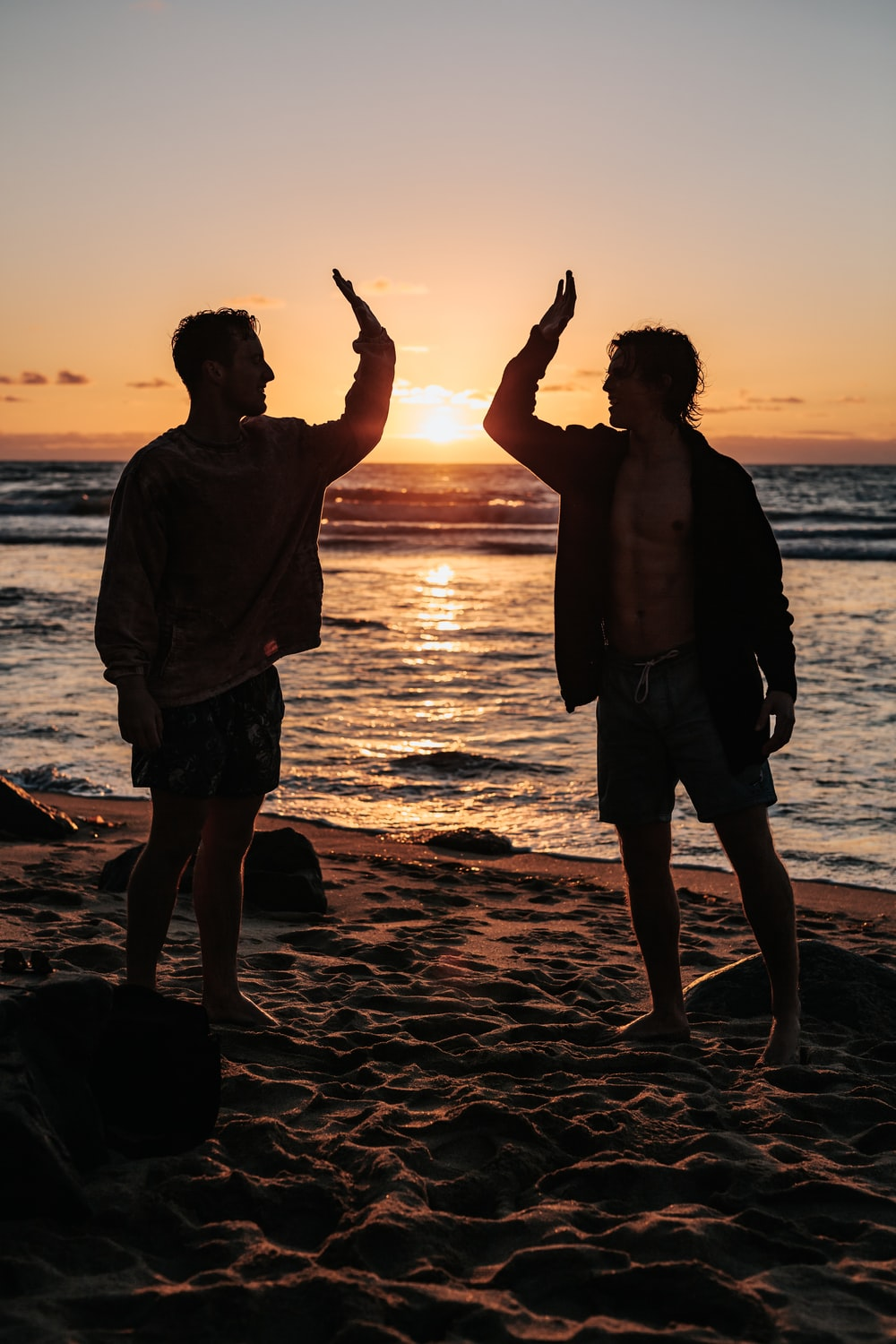 silhouette of two mens near seashore about to high five during sunset
