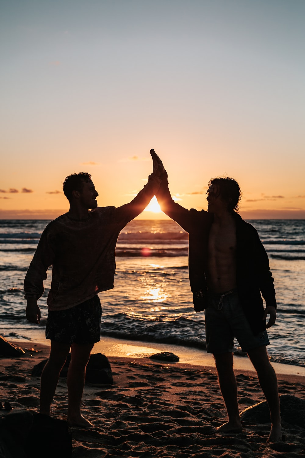 two men clapping each other on shore